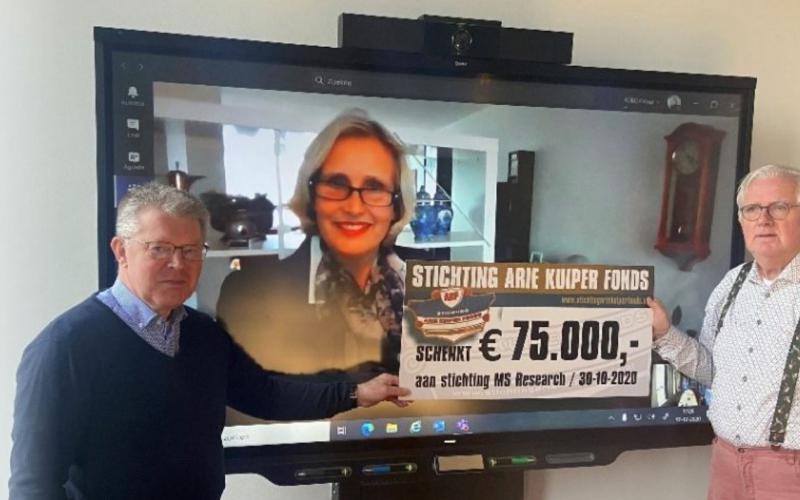 Bestuursleden van het Arie Kuiper fonds overhandigen online een cheque aan directeur van Stichting MS Research.   Beeld: website MS Research